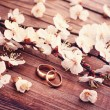Wedding rings. Flowering branch flowers on wooden surface. — Stock Photo #45007729