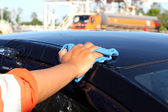 Cleaning black car by hand — Stock Photo
