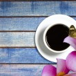 Flower and coffee cup wooden background — Stock Photo #50252717