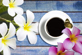 Flower and coffee cup wooden background — Stock Photo