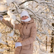 Girl holds on snowy tree — Stock Photo #40991015