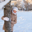 Stock Photo: Girl behind tree in winter