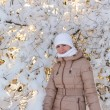Girl stands near snow tree — Stock Photo #40991413