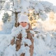 Stock Photo: Young girl smiling near snowy spruce