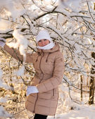 Girl holds on snowy tree — Stock Photo
