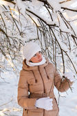 Girl examines a snowy tree — Stock Photo