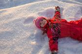 Malá holčička ležet ve sněhu — Stock fotografie