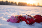 Little girl lying in the snow — Stock Photo