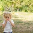 Cute shy little girl in a park - Stock Photo