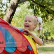 Laughing little girl with tent — Stock Photo