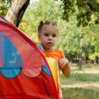 Little girl peering around small tent — Stock Photo #12789020