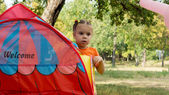 Little girl peering around a small tent — Stock Photo