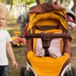Little child alongside an empty pushchair - Stock Photo