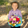 Smiling young boy holding flowers — Stock Photo