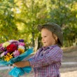 Little boy holding out floral bouquet — Stock Photo #12899404