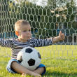 Little boy with ball giving thumbs up — Foto de Stock