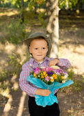 Mischievous little boy with flowers — Stock Photo