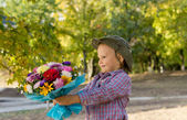 Little boy holding out a floral bouquet — Stock Photo