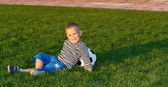 Small boy lying on green grass — Stock Photo