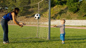 Mother and son throwing a ball — Stock Photo