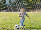 Little boy kicking a goal — Stock Photo