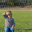 Little boy sitting in goalposts — Stock Photo