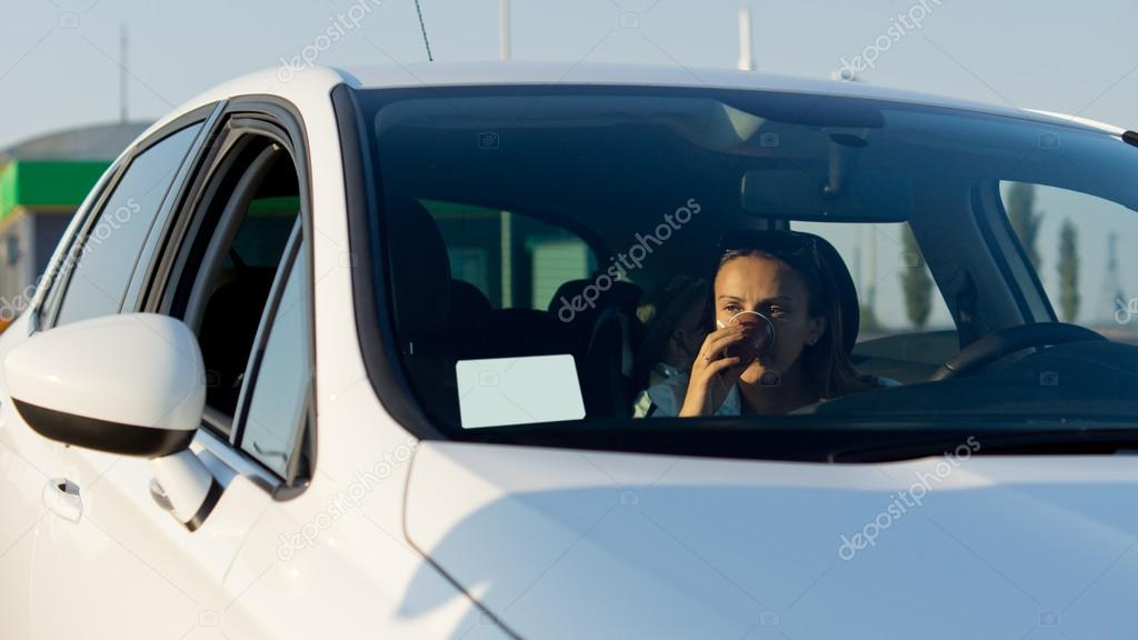 Woman driver in the car with her hand to her face as she looks at a blank sheet of paper on the windscreen of her car — Stock Photo #13068970