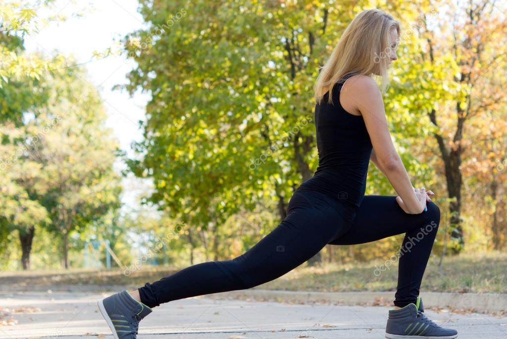 Side view of a fit shapely young blonde woman stretching during a workout in a park  Stock Photo #13326376