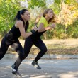 Stock Photo: Two women spring into action during training