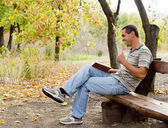Man sitting laughing and reading — Stock Photo