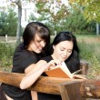 Girls sitting reading a book — Stock Photo