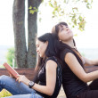Stock Photo: Young friends relaxing on a bench