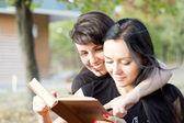 Women laughing at a book — Foto de Stock