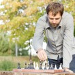 Man playing chess outdoors - Stock Photo