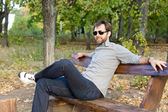 Smiling man relaxing on a park bench — Stock Photo