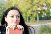Woman sitting daydreaming with her book — Stock Photo