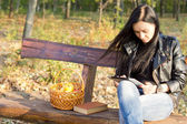 Woman on park bench using a tablet — Stock Photo