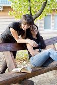 Zwei freunde lachen über ein buch — Stockfoto