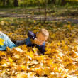 Young children playing in autumn leaves — Stock Photo