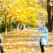 Little girl and boy in autumn park — Stok fotoğraf