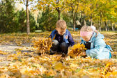 Children playing in a carpet of autumn leaves — Stock Photo