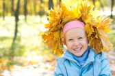 Laughing child wearing yellow autumn leaves — Stock Photo