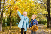 Young Children Holding Leaves in Autumn Woods — Stock Photo