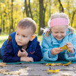 Stock Photo: Small Children Relaxing in a Park in Autumn