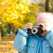 Small girl taking a photograph — Stockfoto