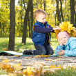 Little boy making an autumn hat for his sister — Stock Photo