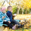 Kids having a snack in an autumn park — Stock Photo #14073790