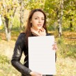 Woman holding a blank sign in woodland — Stock Photo #14151100