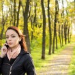 Woman in a park talking on her mobile — Stock Photo