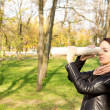 Woman using a rolled newspaper as a spyglass — Stock Photo #14151165